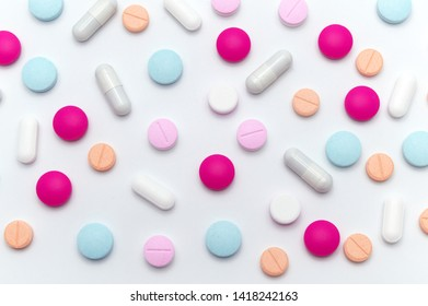 Different colorful pills or supplements for the treatment and health care on a white background.