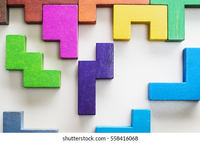 Different colorful shapes wooden blocks on beige background, flat lay. Geometric shapes in different colors, top view. Concept of creative, logical thinking or problem solving.