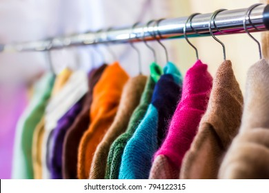 Different colorful woolen knitted women's sweatshirts on the shoulders in the retail clothing store. Selective focus.