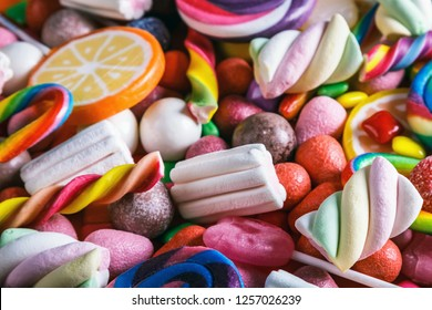 different colors of candy, lollipops, chewing gum, marshmallow and other sweets. The background is sweet