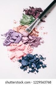 Different colors of crushed eye shadows on white background and make-up brush.