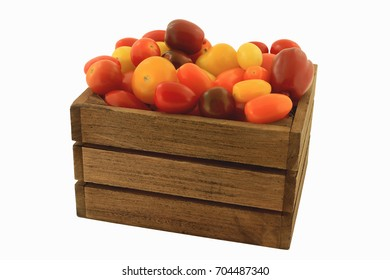 Different colors (red, yellow, orange, brown, Colorful) and shapes Organic mini tomatoes in wooden crate over white background
