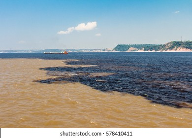 Different colors waters, from the rivers Negro and Solimoes, mingling in front of Manaus port, in Brazil.