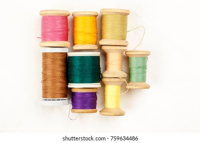 Different colour thread on wooden spools on a white background