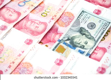 Different concept with one hundred US dollar bill in pile of one hundred Chinese yuan bills on white background. Leadership of Business, finance and economic leader competition between USA and China.