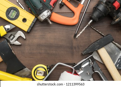different construction tools on wooden background with copy space. top view of diy construction tools on the brown table. close-up of many reparing tools making up a frame