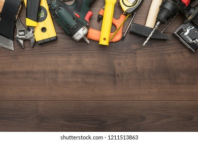 different construction tools on wooden background with copy space. diy construction tools on the brown table