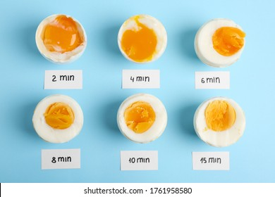 Different cooking time and readiness stages of boiled chicken eggs on light blue background, flat lay