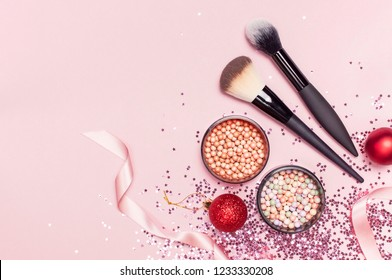 Different Cosmetic makeup brushes, blush powder balls, christmas balls, holographic glitter confetti in the form of stars on pink background Flat lay top view copy space. Makeup accessories, holiday