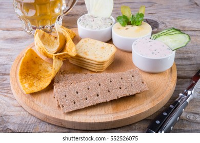 Different crackers with dipping sauce on wooden board