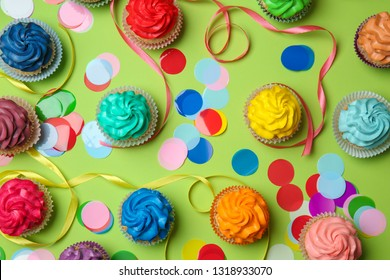 Different cupcakes on color background
