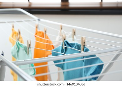 Different cute baby onesies hanging on clothes line indoors. Laundry day
