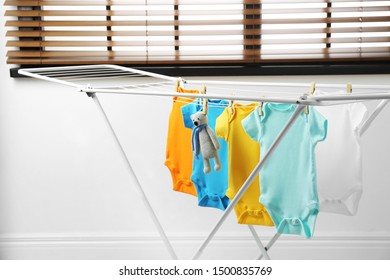 Different cute baby onesies and toy bear hanging on clothes line. Laundry day