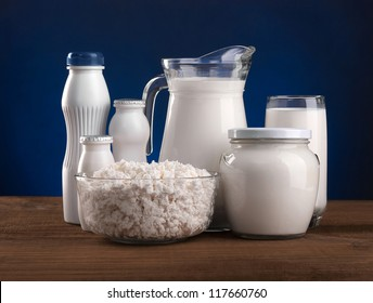 Different dairy products: cheese, sour cream, milk, yogurt, kefir. On a blue background.