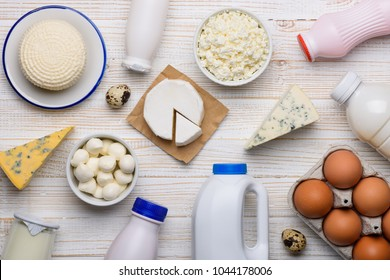 Different dairy products on white wooden table flat lay top view