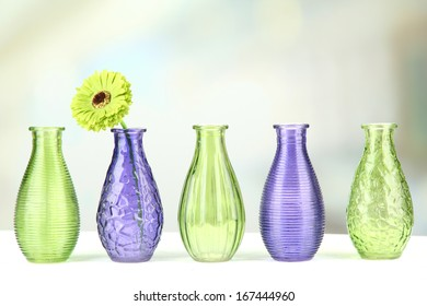 Different decorative vases on shelf on light background