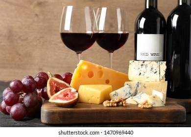 Different delicious cheeses, fruits and wine on table against wooden background