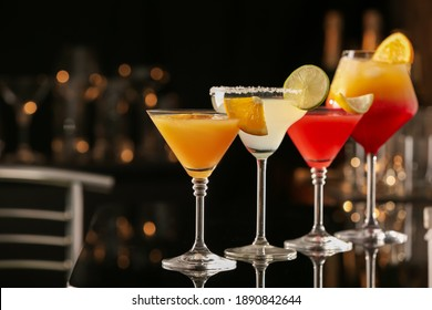 Different delicious cocktails on black table in bar. Space for text