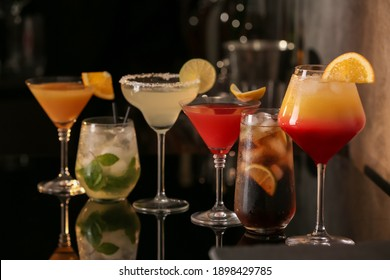 Different delicious cocktails on black table in bar