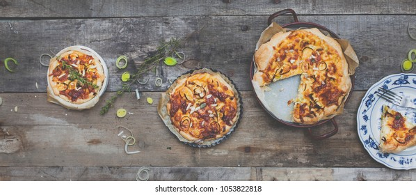 different delicious quiches on a wooden background