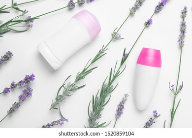 Different deodorants and lavender flowers on white background, top view