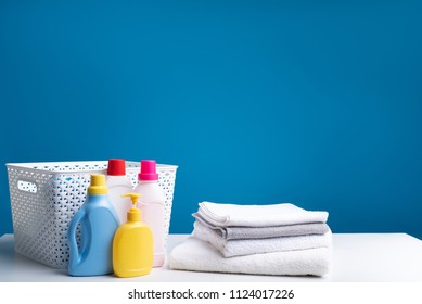 Different detergents standing on white table with clothesbasket behind. Heap of light soft linens lying nearby