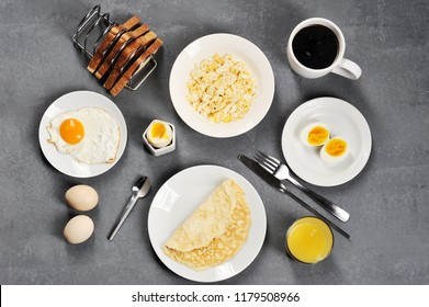 Different dishes from chicken eggs. Omelette, soft-boiled, hard-boiled, fried, scrambled eggs. In the frame bread toast and a cup of coffee. Close-up. View from above. Gray background.