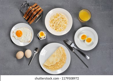 Different dishes from chicken eggs. Omelette, soft-boiled, hard-boiled, fried, scrambled eggs. In the frame, toasts and a glass of juice. Close-up. View from above. Gray background.
