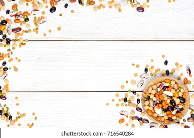 Different dry legumes on white wooden background, top view. Copyspace background.