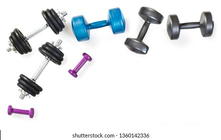 Different dumbbells composition on white background. Professional metal dumbbells and fitness dumbbells. Sport accessories. Top view. Frame.