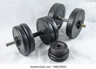 Different dumbbells with plastic dumbbells filled with concrete and additionally different small dumbbell discs