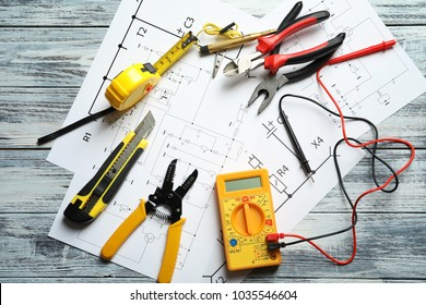 different electrical tools and circuit diagram on wooden background