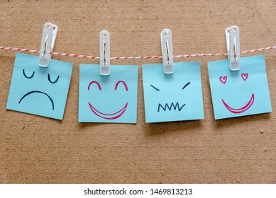 Different emotion faces drawing on sticky notes on blank board, positive and negative attitude, happy and unhappy, love and confused concept.