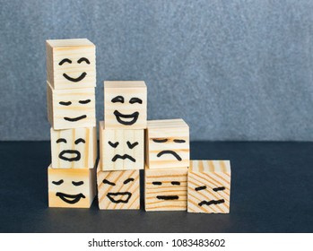 Different emotions drawn on wooden cubes on the dark background.