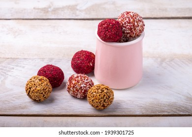 Different energy balls on a wooden white background.