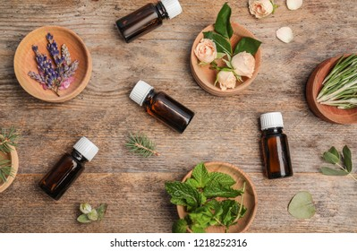 Different essential oils and ingredients on wooden background, flat lay