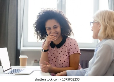 Different ethnicity and ages colleagues friends take break from work laughing chatting informal talk, office workers sitting at desk telling jokes share humorous stories, have fun in workplace concept
