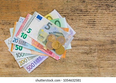 Different Euro banknote money and coins. Set of 500 200 100 50 20 10 5 European currency on weathered wooden background