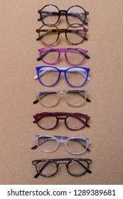 Different eyeglass frames on cork board