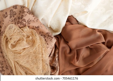 Different fabrics. Organza, chiffon, silk, jacquard are spread out on the table. View from above. Beige silk, brown organza, golden mesh fabric for sewing clothes. Design of fabric. Fashionable fabric
