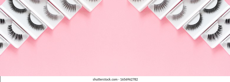 Different fake eyelashes on a trendy pastel pink background. Beauty pattern. Makeup accessories. Cosmetics products for women. Top view, flat lay. Layout. Copy space. Place for text and design. Banner