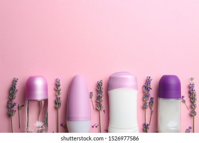 Different female deodorants and lavender flowers on pink background, flat lay. Space for text