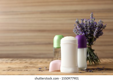Different female deodorants and lavender flowers on wooden background, space for text