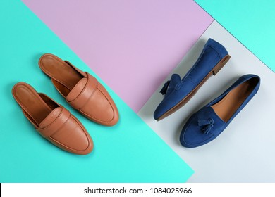 Different female shoes on color background, top view