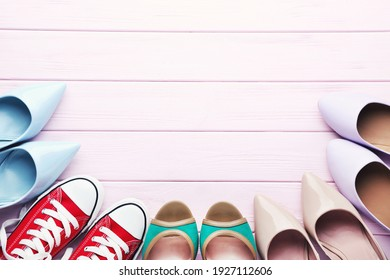 Different female shoes on pink wooden table