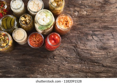 Different Fermented preserved vegetables in glass jars on a rustic wooden background  with copy space