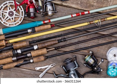 different fishing rods and reels on wooden boards background. creative idea for design tackle service, repair.