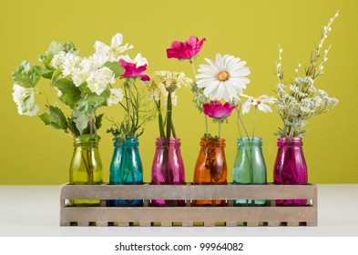 Different flowers in colorful vases on a white table in front of a green background