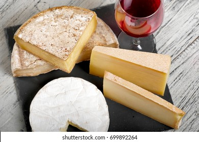Different french cheeses with a glass of red wine