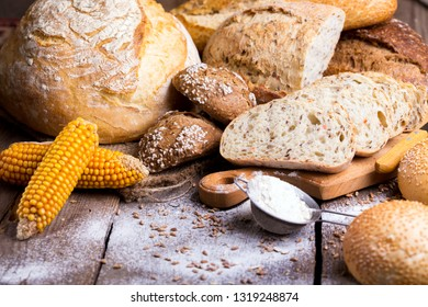 different fresh bread and buns on the wooden table